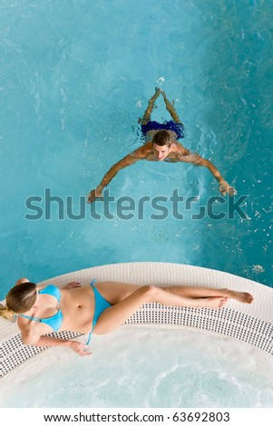 Top view - young couple relax in swimming pool sitting at bubble bath