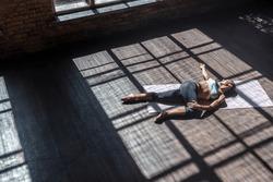 Top view young sporty fit woman practice hatha yoga instructor lie supine spinal twist posture Supta Jathara Parivartanasana pose modern gym mat wooden floor window healthy lifestyle concept.