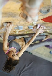 Top view Young Woman Rock climber is Climbing At Inside climbing Gym. slim pretty Woman Exercising At Indoor Climbing Gym Wall. Slender fitness pretty woman making some hard moves