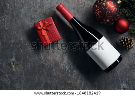 Top viiew of bottle of red wine with blank white label with Christmas decorations and gift box on dark background. Wine bottle mockup.
