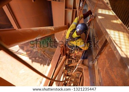 Tope view abseiler rope access repairer wearing safety fall body harness protection, helmet standing, hanging in fall restraint position performing oxy acetylene cutting metal beam construction site