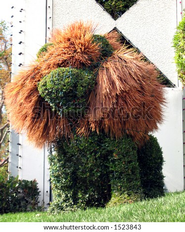 Topiary of a lion with Christmas lights draped all over it. - stock photo