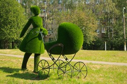 topiary sculpture of mother with stroller made of grass. Urban design, city architecture, park decoration. Figure of female walking with her newborn child.