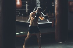 Topless athlete is training defense and attacks in sport center. He is kicking punching bag while using gloves and moving around. Man is having cardio boxing workout