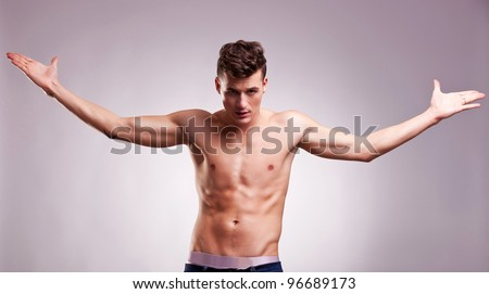 topless young fashion model with his hands in the air at his sides on gray background. muscular young man with arm outstretched