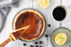 Topview of basque burnt cheesecake serve with black coffee on white wooden table.