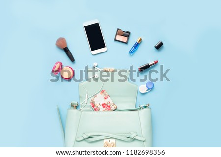 Topview of Fashionable female accessories watch glasses lipstick perfume and blue bag. Overhead of essentials for any girl, on blue background #1182698356