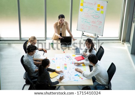 Topview of Smart Asian Business female leader in a casual meeting with her teamwork colleagues at the modern desogn office presenting sales strategy plan and data, forecast for project goal schedule.