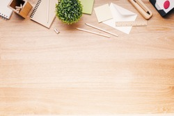 Topview of wooden desk with office tools and plant. Mock up