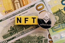 Topview photo on NFT (non-fungible token) theme. Abbreviation NFT and Ethereum blockchain cryptocurrency coin, on the background of dollar and euro banknotes