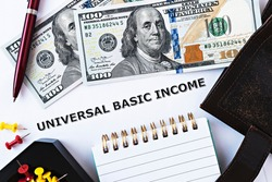 Topview photo on Universal Basic Income theme. The words Universal Basic Income on paper, surrounded by dollar banknotes, notepad, wallet and red pen