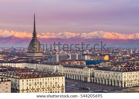 Shutterstock Torino (Turin, Italy): cityscape at sunrise with details of the Mole Antonelliana towering over the city. Scenic colorful light on the snowcapped Alps in the background.