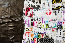 Torn and crumpled black glossy paper poster on bright colorful collage of magazine paper pieces and clippings with letters and numbers background.