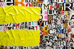 Torn and crumpled pieces of yellow paper on collage from clippings with newspaper magazine letters and numbers. Ripped yellow paper glued on alphabet letters cutting from magazine background.