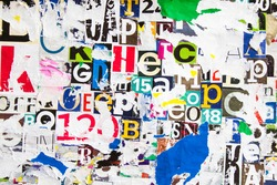 Torn and peeling pieces of paper on colorful collage from clippings with letters and numbers texture background.