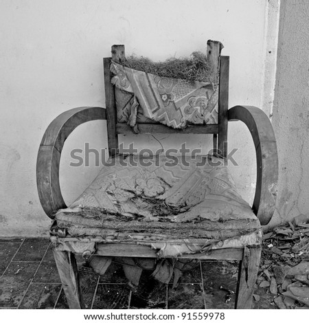 Torn armchair and pile of broken glass. Black and white.