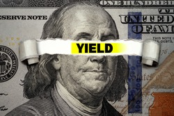 Torn bills revealing YIELD words. Ideas for US Dividend yield, stocks and funds, Passive income, US dollar ETF, Investing for incomes, Dividend calculator, Buy and Hold, Stable income, Finance concept