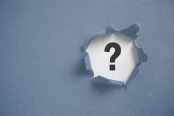 Torn grey paper with question mark. Question mark concept.