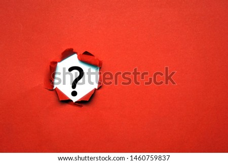 Torn out red paper with question mark symbol