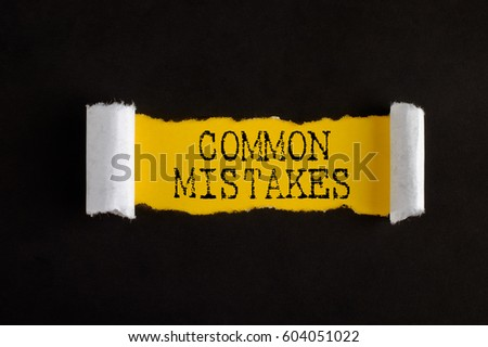 Torn paper with text COMMON MISTAKES, business concept.