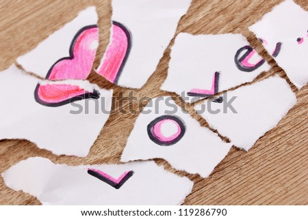 Torn paper with words Love close-up on wooden table
