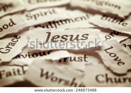 Torn paper words of religion with focus on word Jesus