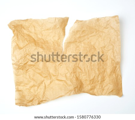 torn piece of brown piece of parchment paper on white background
