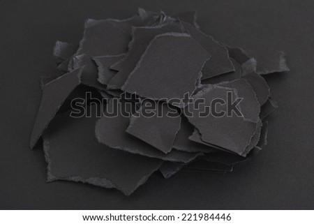 Torn pieces of black paper on a black background.