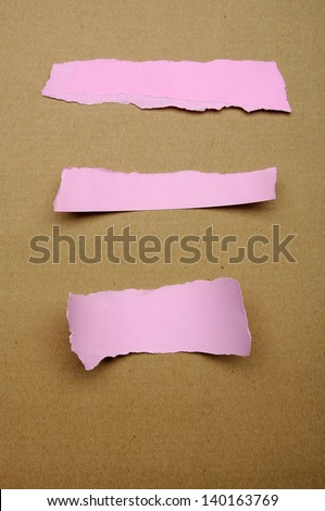 Torn pink paper scraps on brown cardboard background. You can put your design on the paper