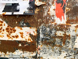 Torn poster on rust metal texture. Old grungy street wall with ripped rock concert advertisements. Rough abstract background for street urban art.