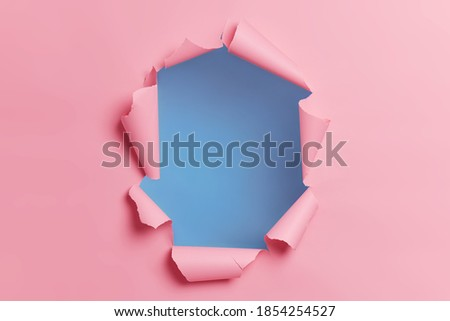 Torn ripped pink background with hole in center for your advertising content or promotion. Blank space to insert object. Absract horizontal shot. Breakthrough concept. Nobody at image. Through paper Foto stock ©