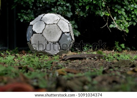 Torn up old soccer ball lay on grass. Worn out football. Concept of inactive person or useless object.