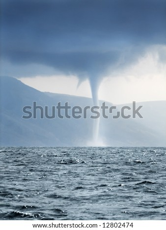 Tornado and storm clouds forming over rough sea