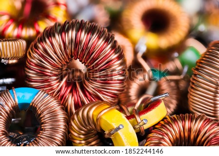 Toroidal electronic inductors on heap in electrotechnical background. Closeup of beautiful induction coils with copper wire winding on magnetic ferrite core. Colored electrical engineering components. Stok fotoğraf ©