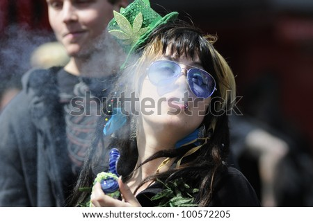 TORONTO - APRIL 20:  A Marijuana smoker blowing off smoke  during the annual marijuana 420 event at Yonge & Dundas Square  on April 20  2012 in Toronto, Canada.