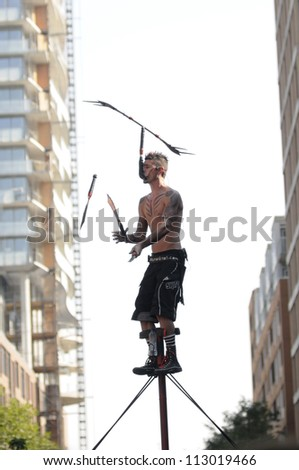 TORONTO-AUGUST 31: A  performer juggling with swords while high up in the air during the Buskerfest Festival on June 31, 2012 in Toronto, Canada.