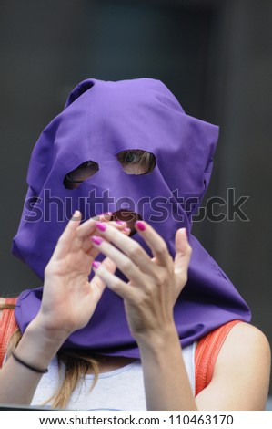 "TORONTO -AUGUST  17:  A Pussy Riot supporter clapping  during a protest rally organized to free ""pussy riot""on August 17 2012 in Toronto, Canada."