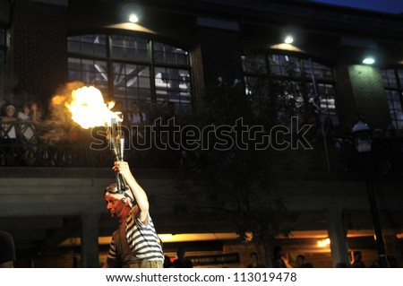 TORONTO-AUGUST 24: A street performer holds a lighted torch during the Buskerfest Festival on August 24, 2012 in Toronto, Canada.