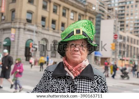 TORONTO, CANADA - March 13, 2016:  St. Patrick's Day Parade in the downtown of Toronto. Older woman in fun leprechaun hat enjoying the Irish parade spirit.
