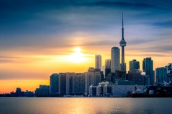 TORONTO CITY SKYLINE AT SUNSET - Beautiful scene of Toronto cityscape with gorgeous sunset sky and clouds. Tight shot of Toronto downtown city buildings with warm sunlight. Toronto, Ontario, Canada