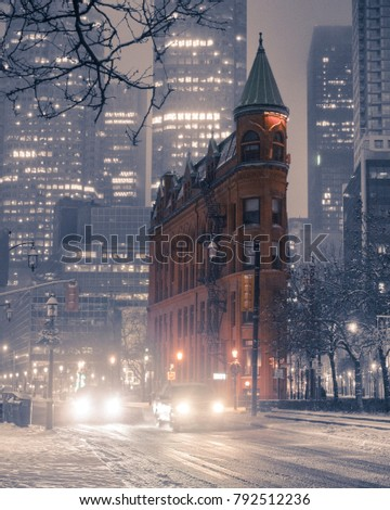 Toronto Gooderham Building during snow storm at night with downtown buildings and urban city setting in background. Historic architecture. Flatiron building. Toronto, Ontario, Canada