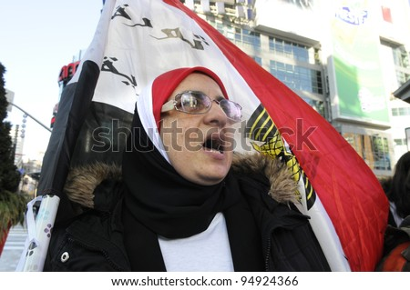 TORONTO - JANUARY 21: A old Egyptian woman chanting slogans in a rally at Yonge and Dundas square during the global day of support for the Egyptian revolution on January 21 2012 in Toronto, Canada.