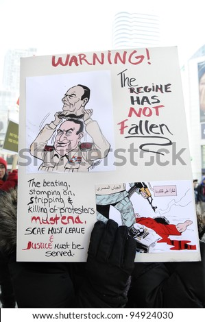 TORONTO - JANUARY 21: A protestor holding a cartooned placard denouncing killing of protesters during the global day of support for the Egyptian revolution on January 21 2012 in Toronto, Canada.