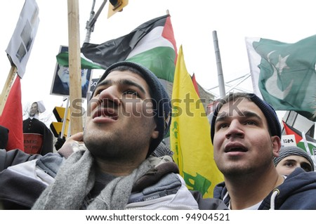 TORONTO - JANUARY 10:   Two Arab brothers listening to the speakers during a rally to condemn the Israel occupation on Gaza on January 10 2009 in Toronto, Canada.
