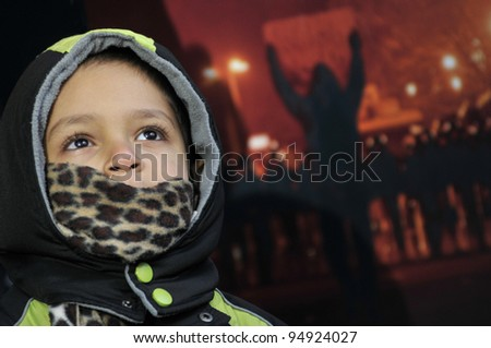 TORONTO - JANUARY 21: 4 year-old  unidentified Yemeni standing in front of a poster showing the Egyptian uprising during the global day of support for the Egyptian revolution on January 21 2012 in Toronto, Canada.