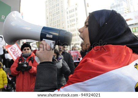 TORONTO - JANUARY 21:   Young Egyptians chanting slogans at Yonge and Dundas square during the global day of support for the Egyptian revolution on January 21 2012 in Toronto, Canada.