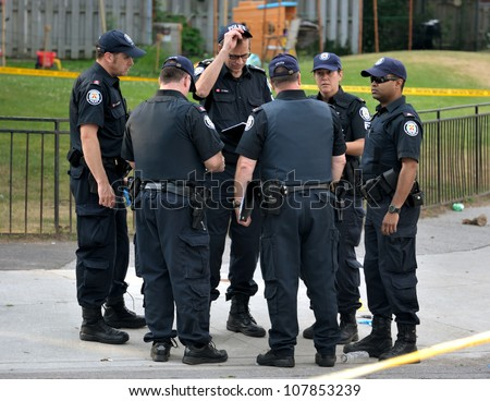 TORONTO-JULY 17: A group of police officers at the crime scene where shooting leaves 2 dead and 21 injured on July 17, 2012 in Toronto