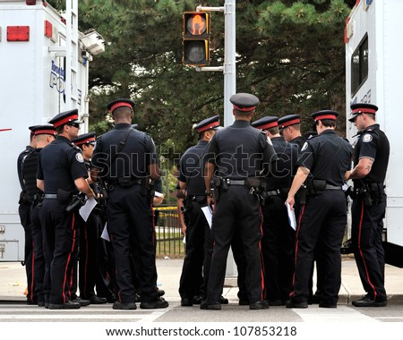 TORONTO-JULY 17: A group of police officers taking orders at the crime scene where shooting leaves 2 dead and 21 injured on July 17, 2012 in Toronto