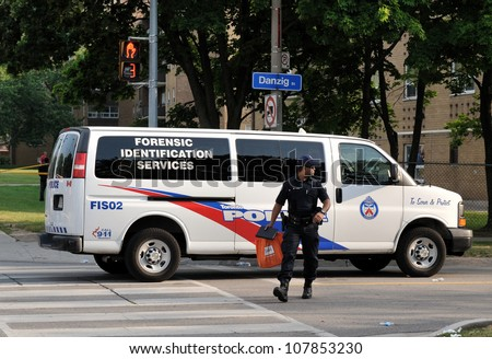 TORONTO-JULY 17: A Police officer from Toronto Forensic Identification Services Unit  at the crime scene where shooting leaves 2 dead and 21 injured on July 17, 2012 in Toronto