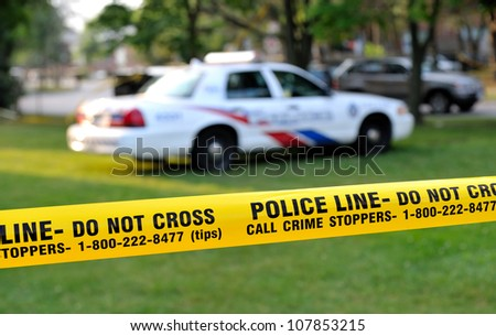 TORONTO-JULY 17: Police line Do not cross tape with police car in the background at the crime scene where  shooting leaves 2 dead and 21 injured on July 17, 2012 in Toronto